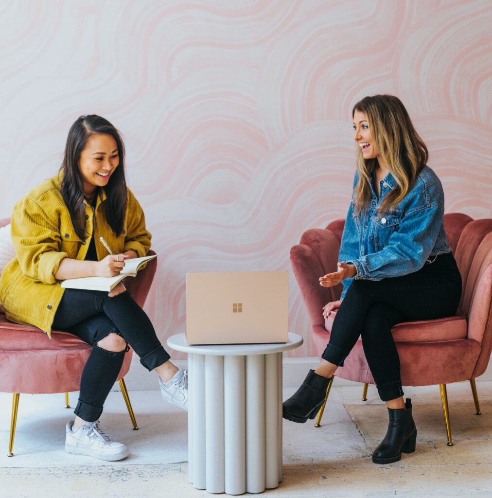 Two girls sitting in front of computer